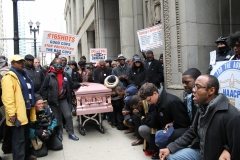 protesters-sat-down-in-front-of-city-hall-doors-and-prayed-coffins-in-view